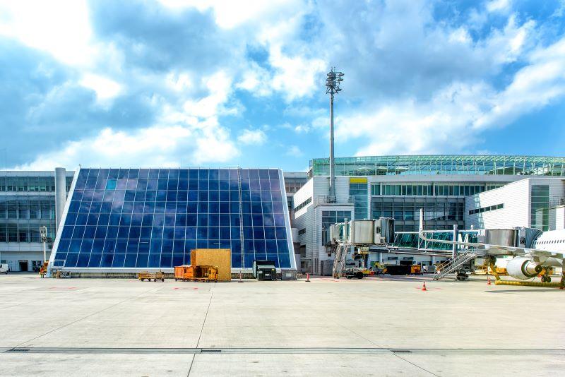 Flughafengebäude mit großflächiger Photovoltaik vom Rollfeld aus.