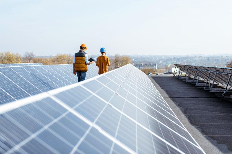 Flachdach mit Photovoltaikanlage, Ingenieure zwischen den Reiehne