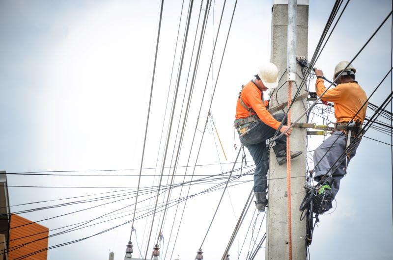 Zwei Arbeiter auf einem Strommast mit Leitungen in vielen Richtungen.