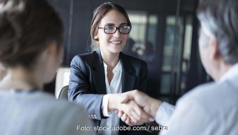 Eine junge Frau im Anzug, lächelnd und Kunden die Hände schüttelnd.