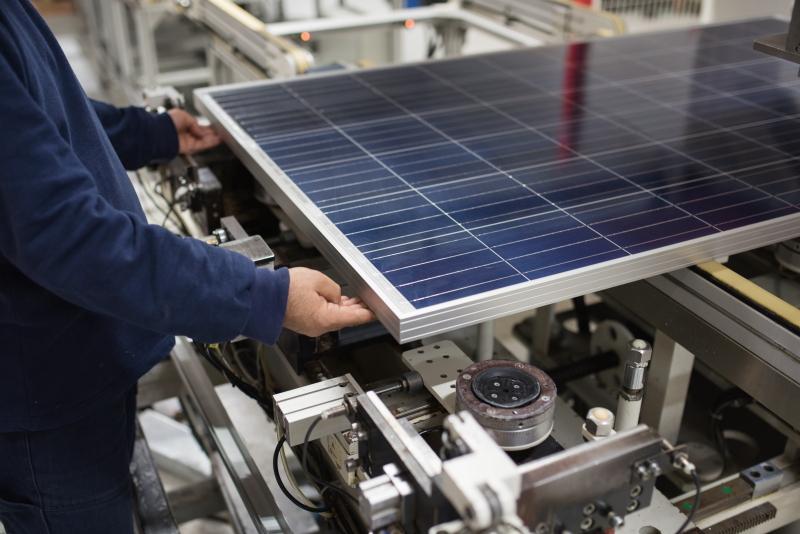 Arbeiter mit einem Solarmodul in einer Fabrik an einer Maschine.