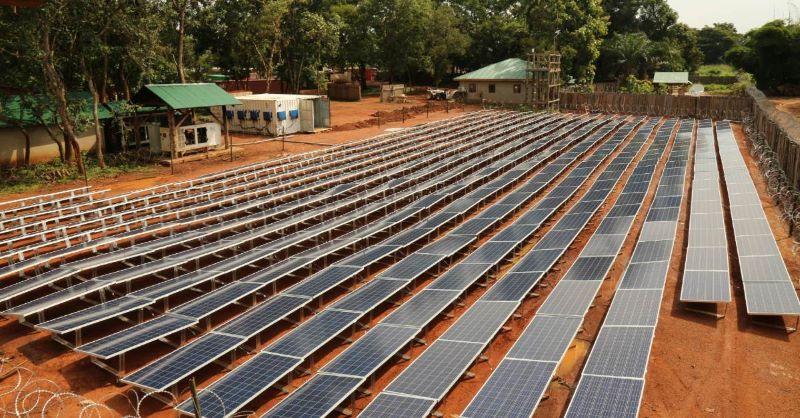 Ein PV-Feld auf roter Erde und mit technischer Peripherie in einer ländlich gepägten Landschaft.