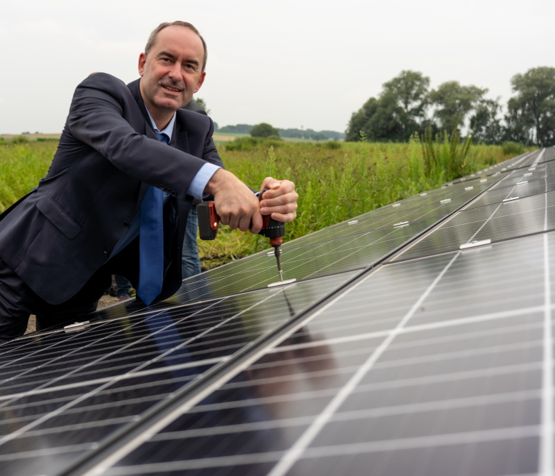 Bayerns Wirtschaftsminister Hubert Aiwanger bei der Montage eines Moduls an einer Solaranlage im Freien.