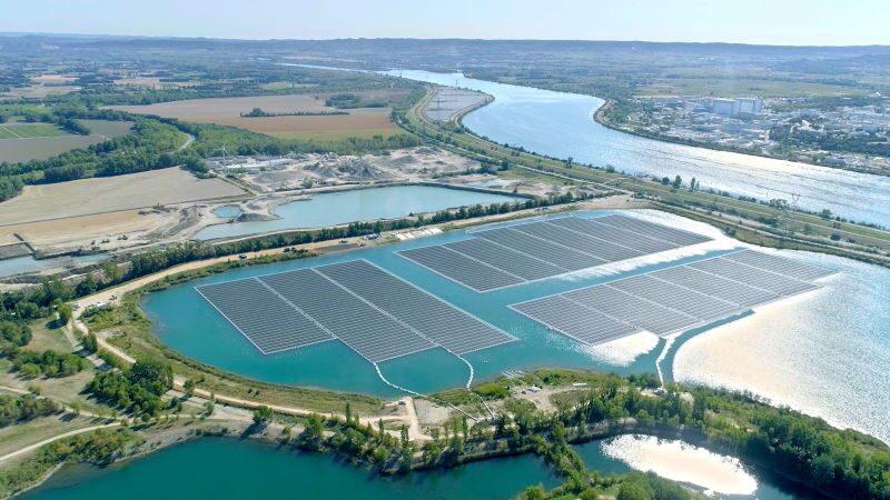 Die Luftaufnahme zeigt Reihen von Solarmodulen auf einem von mehreren Seen. Der See ist durch einen Erdwall und eine Straße vom Fluss Rhone getrennt