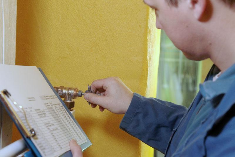 Handwerker stellt für hydraulischen Abgleich ein Heizkörperventil ein