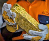 Minenarbeiter hält Goldbarren in den Handschuh-Händen.