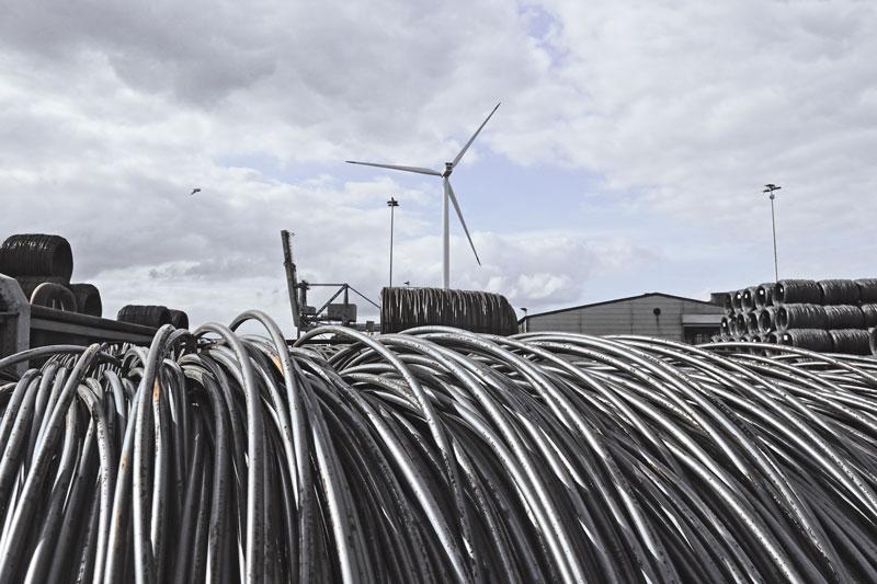 Im Vordergrnd Stahlseile, im Hintergrund das Stahlwerk mit einem Windrad. Hier soll auch Wasserstoff zum Einsatz kommen.