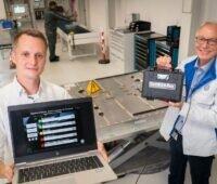 Zu sehen sind die Audi-Mitarbeiter Robin Krause und Joachim Wöhle, die mit Battman ReLife E-Auto-Batterien auf ihre Tauglichkeit zum Second Lift testen.