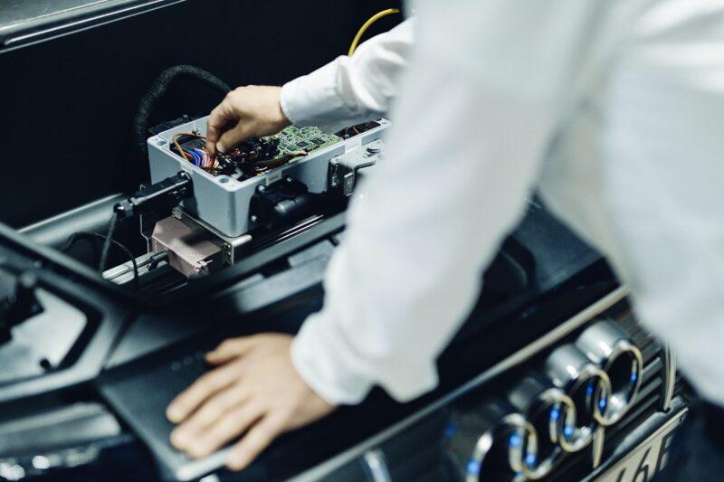 Zu sehen ist der offene Motorraum eines E-Audi, an dem bidirektionales Laden erforscht wird.