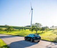 Zusehen ist ein Audi e-tron Elekotrauto bei einer Testfahrt mit einem Windrad im Hintergrund. Audi testet zurzeit das Batterierecycling.