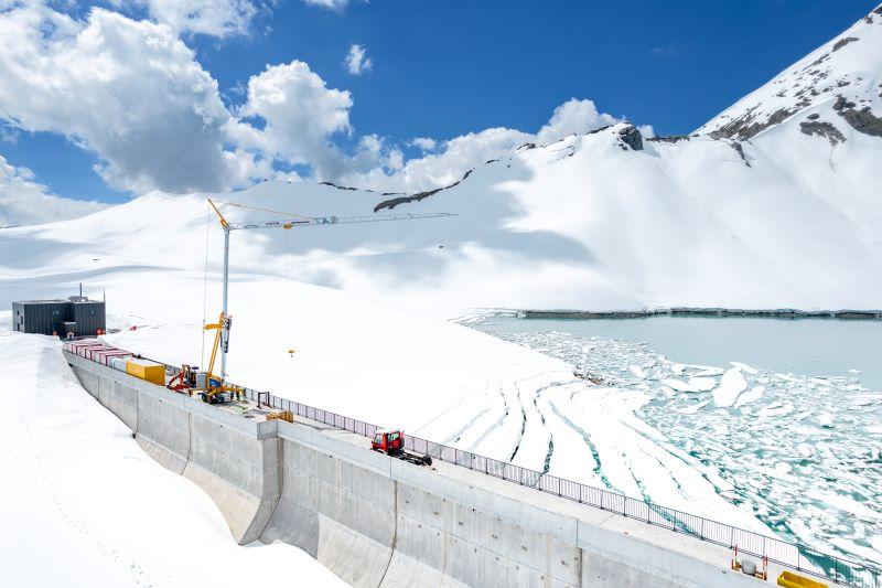 Bauarbeiten an einer Staumauer umgeben von Schnee.