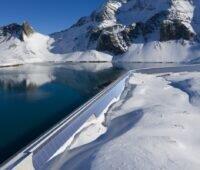 Zu sehen ist die geplante Photovoltaik-Anlage an der Muttsee-Staumauer als Visualisierung an der realen Staumauer in der schneebedeckten Berglandschaft.