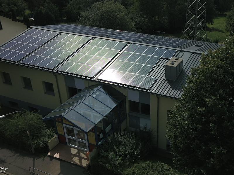 Blick auf das Dach einer Kita mit Solarmodulen.