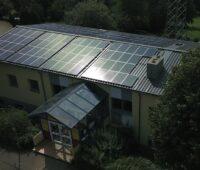 Eine Solaranlage auf dem Dach einer Kita bei tiefstehender Sonne,