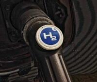 Zu sehen ist ein Auto, das mit Wasserstoff betankt wird als symbolische Darstellung für die Reduktion der EEG-Umlage bei der Wasserstoff-Herstellung.