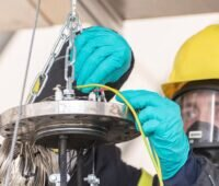 Ein Arbeiter ,it Schutzkleidung testet eine Lithium-Ionen-Batterie
