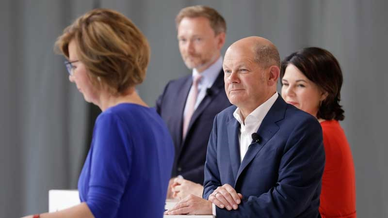 Zu sehen sind Olaf Scholz, Annalena Baerbock und Christian Linder beim BDEW-Talk zur Bundestagswahl. Im Vordergrund BDEW-Präsidentin Wolff, die ein ressortübergreifendes Klimaschutzministerium fordert.