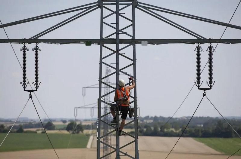 Zu sehen ist ein Arbeiter, der auf einen Strommast einer Hochspannungsleitung klettert. Die Bundesnetzagentur setzt die Eigenkapitalkosten für Strom- und Gasnetzbetreiber fest.