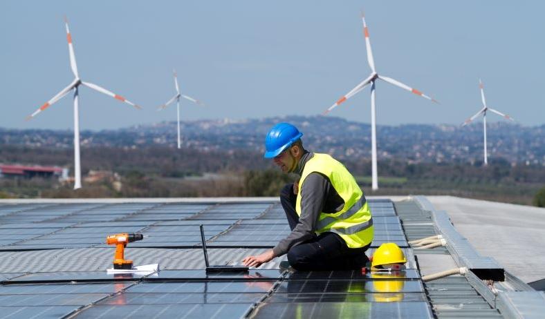 Zu sehen ist die Montage einer Photovoltaik-Dachanlage, im Hintergrund sind Windenergieanlagen. Die BMWi-Langfristszenarien unterschätzen laut BEE die nationalen Potenziale für erneuerbare Energien.