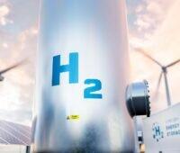 Zu sehen ist eine Montage aus Wasserstofftank, PV und Wind als symbolisches Bild für die EEG-Umlagebefreiung der Wasserstoff-Herstellung.