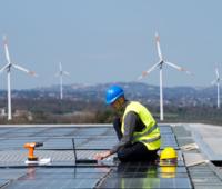 Zu sehen ist die Montage einer Photovoltaik-Anlage vor Windkraftanlagen, deren Ausbau von der beihilferechtlichen Genehmigung des EEG 2021 abhängt.