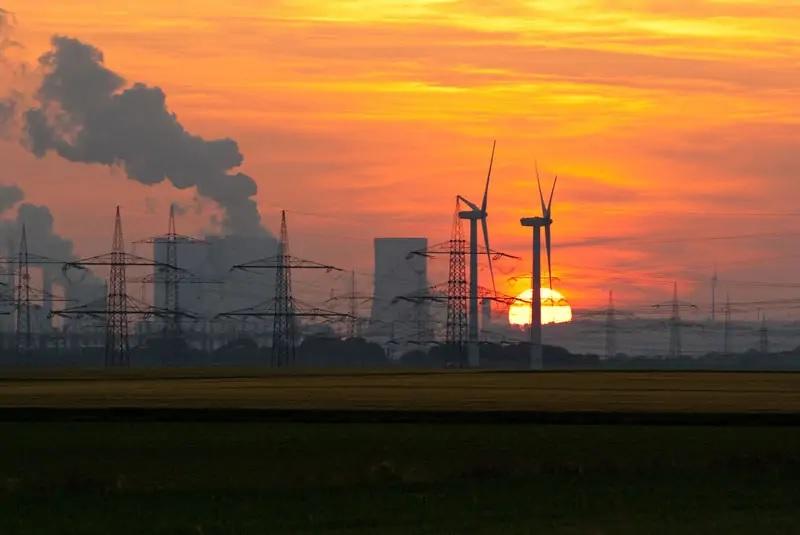 Zu sehen ist ein Kohlekraftwerk im romantischen Abendhimmel mit zwei verlorenen Windkraftanlagen im Vordergrund als Symbol für die handwerklichen Mängel im EEG 2021