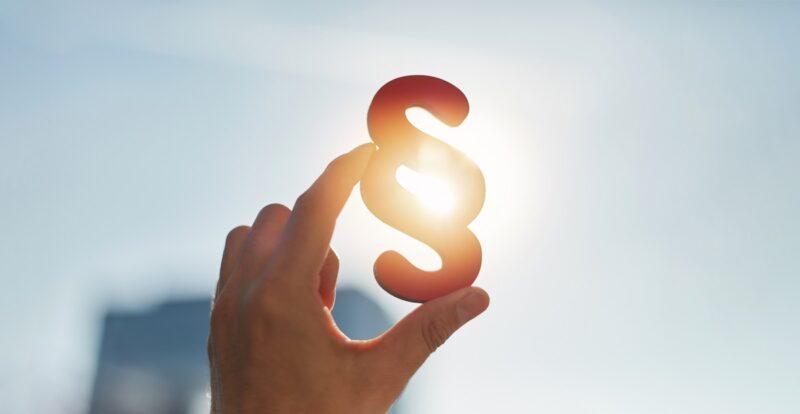 Zu sehen ist ein Paragrafen-Zeichen, das eine Hand in die Sonnen hält, als Symbol für das KWK-Gesetz.