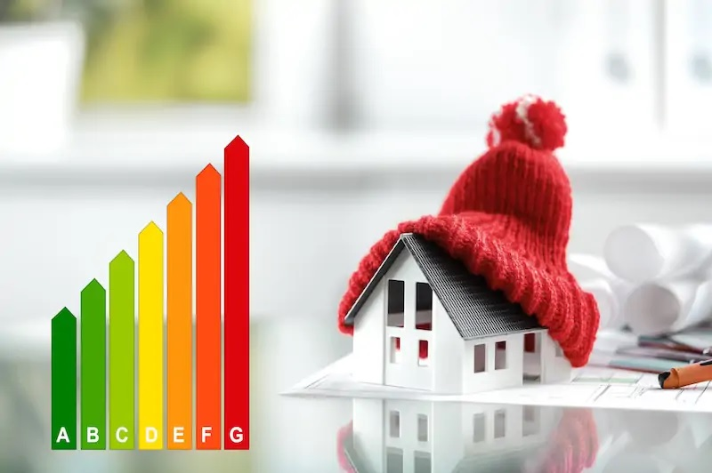 Haus mit Pudelmütze als symbolische Darstellung für die energetische Gebäudesanierung im Rahmen derRichtlinien zur BEG-Förderung.