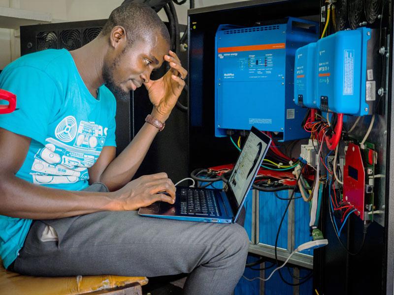Mensch dunkler Hautfarbe arbeitet an Solarelektronik
