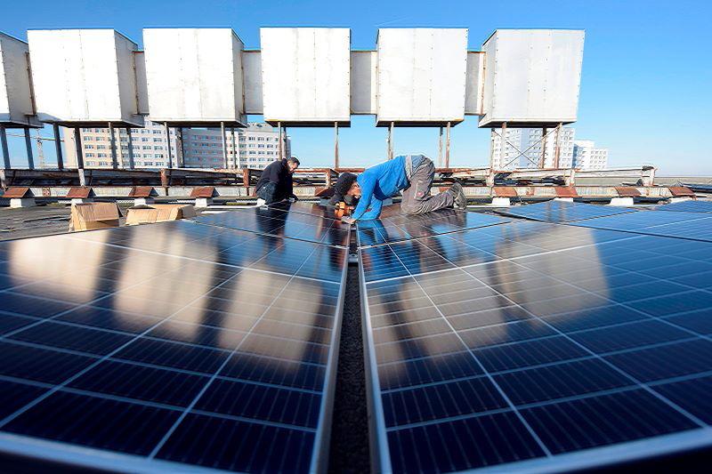 Monteure installieren Photovoltaik auf dem Berliner Verlagsgebäude des Neuen Deutschlands.