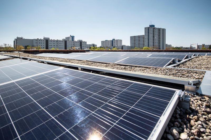 Eine PV-Anlage auf einem Flachdach, in der die Sonne reflektiert.