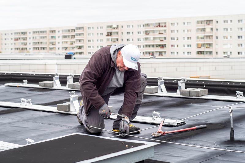 Ein Mann montiert auf einem Hochhausdach Bahnen für Solarmodule.