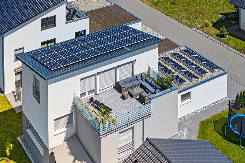 Blick auf Neubausiedlung mit einigen Häuser, die Photovoltaik auf ihren Flachdächern haben.