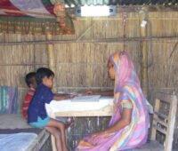 Einer Mutter mit ihren Kindern am Tisch, beleuchtet durch elektrisches Licht.