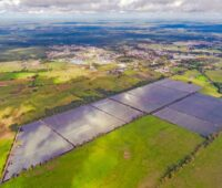 Luftaufnahme eines PV-Parks im landwirtschaftlich geprägten Flachland.