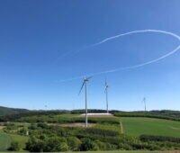 Windkraftanlagen auf welligem Terrain unter blauem Himmel.