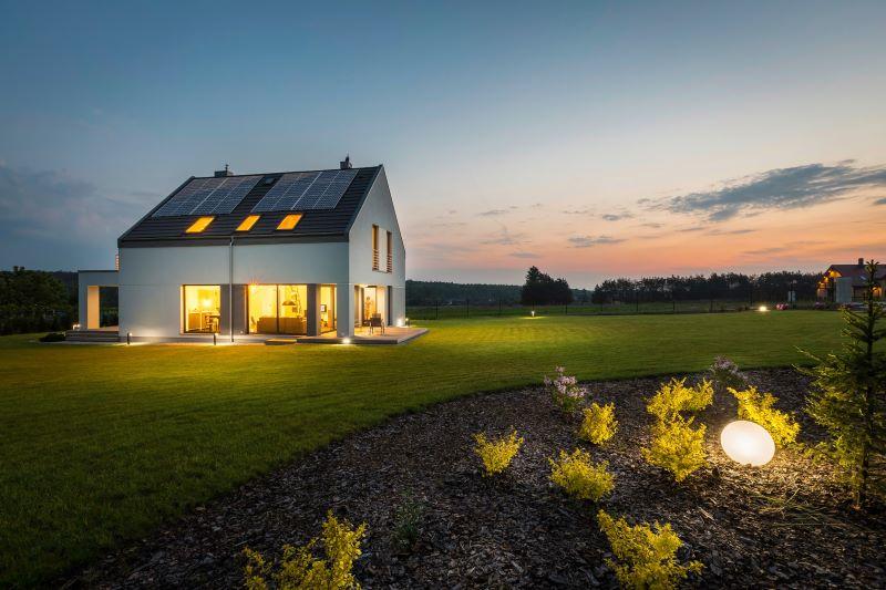Ein beleuchtetes Haus alleinstehend bei spätem Sonnenuntergang