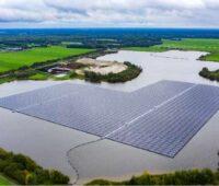 Eine schwimmende PV-Anlage umgeben von Grün.