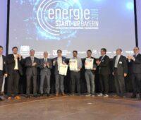 Auf einer Bühne stehen zehn Personen und präsentieren Urkunden vom Byrischen Energiuepreis 2018 für Start-Ups.