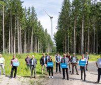 """Zu sehen ist eine Menschengruppe mit Wirtschaftsminister Hubert Aiwanger im Wald vor einer Windenergieanlage bei der Auszeichnung """"Gestalter der Energiewende""""."""