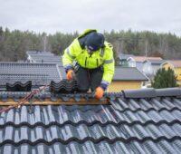 Ein Monteur installiert auf einem Dach Solarziegel, denen man die Solartechnik nicht ansieht.