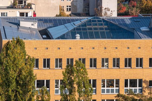 Auf dem verglasten Dach einer Fachhochschule sind Solarmodule installiert