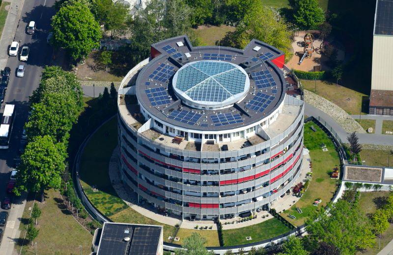 Luftaufnahme des kreisrunden Wohngebaäudes Degnerbogen mit PV-Modulen auf dem Dach.