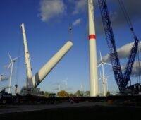 Zu sehen ist der Windenergie-Park in Albertshof der Berliner Stadtwerke in der Bauphase mit einem großen Kran.