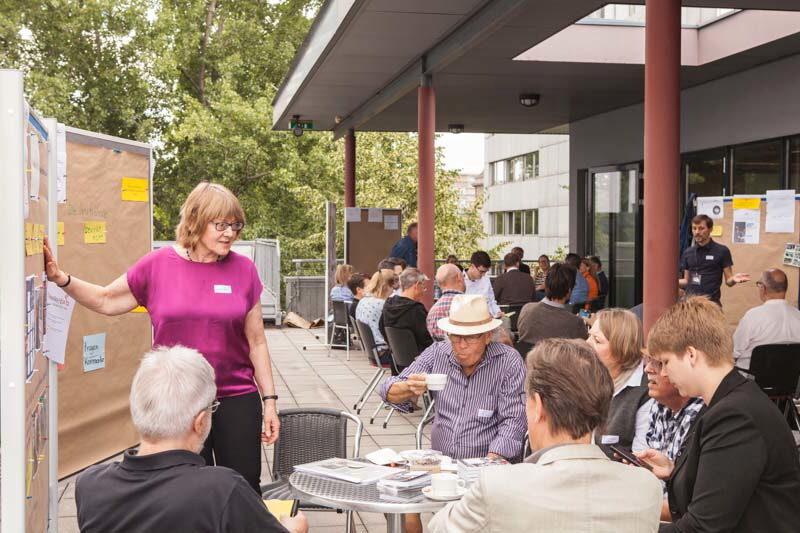 Menschen sitzen an Tischen vor einem Gebäude und trinken Kaffee. Trainer stehen an Schautafeln und erläutern