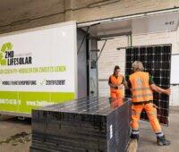 ein grün-weißer Container mit geöffneter Klappe, ein Stapel Photovoltaik-Module und zwei Menschen mit orangefarbenen Anzügen: der mobile Teststand des Recycling-Anbieters Buhck