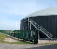 Ein Biogasfermenter steht im Vordergrund, daneben Windkraftanlagen unter blassblauem Himmel.