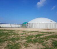 Eine Biogasanlage mit Fermenter unter blauem Himmel.