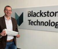 Holger Gritzka, Geschäftsführer der Blackstone Technology GmbH, präsentiert die erste gedruckte Lithium-Ionen-Batteriezelle vor Firmenlogo