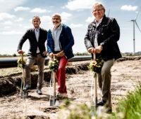 Drei Herren beim Spatenstich in Nordfriesland. Im Hintergrund Windkraftanlagen.